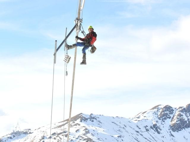 Arbeiter hängt an Seilen mit einem Bauteil