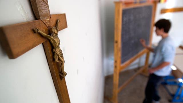 Ein braunes Kruzifix hängt an der Wand, unscharf im Hintergrund ein Schüler, der auf eine Tafel schreibt.