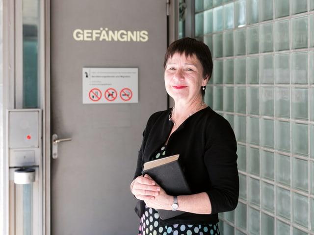 """Eine Frau mit gepunktetem, farbigen Rock steht vor einer massiven Türe, welche die Aufschrift """"Gefängnis"""" trägt."""