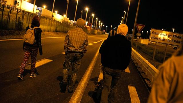 Migrants sin ina via ordaifer l'areal da l'Eurotunnel a Calais en il nord da la Frantscha.