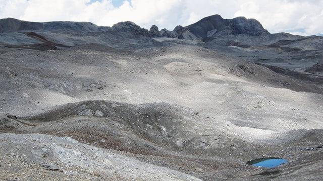 Eine karge Berglandschaft, am unteren Bildrand ein kleiner See.