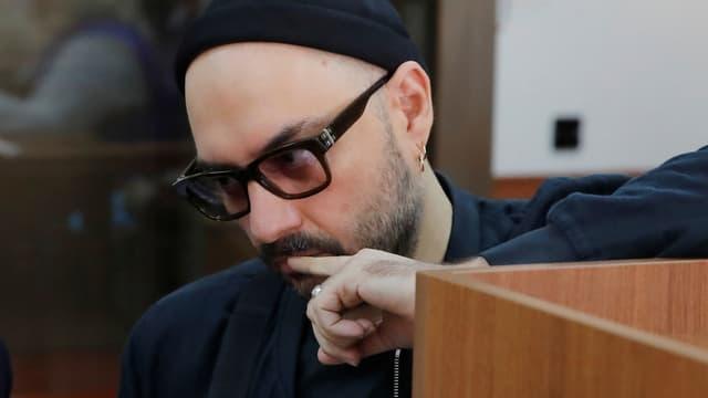 Ein mann mit schwarzer Mütze und schwarzer Hornbrille.