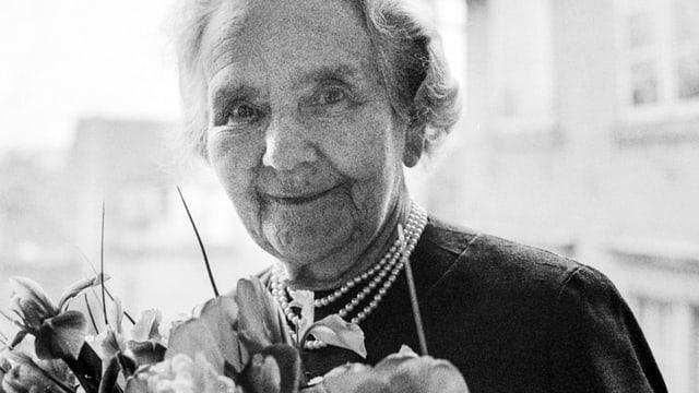 Eine ältere Dame vor einem Blumenstrauss