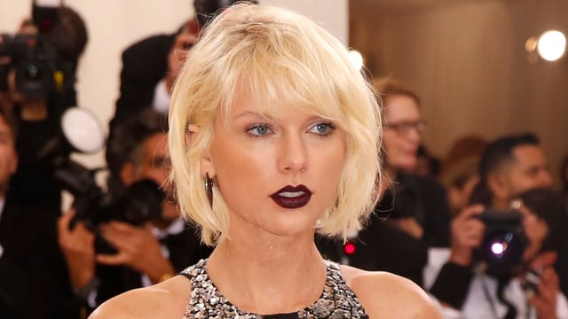 Taylor Swift mit kurzen blonden Haaren und dunklem Lippenstift.
