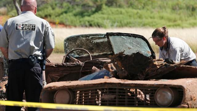 Polizisten untersuchen eines der beiden Autowracks.