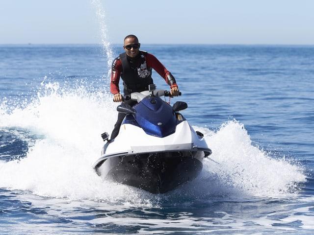 Lewis Hamilton rast mit einem Jet-Ski über das Wasser.