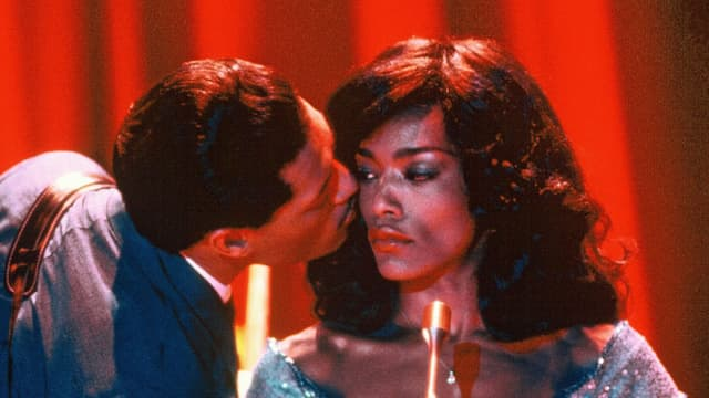 Eine Frau mit ernstem Gesicht, ein Mann gibt ihr einen Kuss auf die Wange.