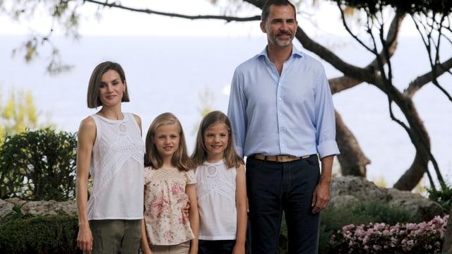 Die Familie posiert zu viert draussen.
