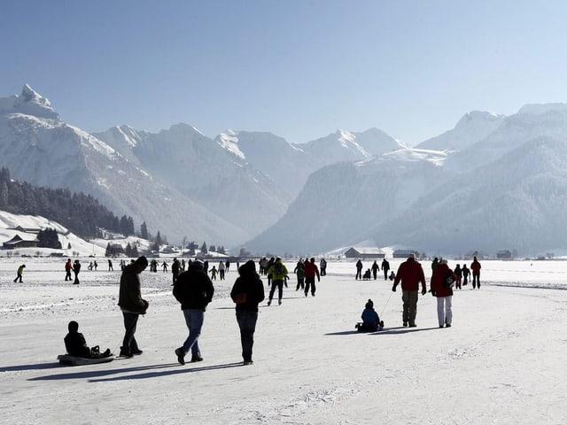 Menschen begehen den gefrorenen Sihlsee im Kanton Schwyz bei strahlendem Sonnenschein. (keystone)