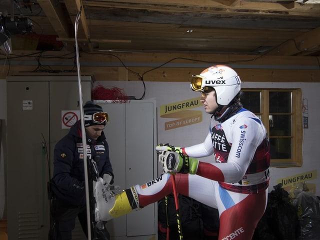 Urs Kryenbühl steht mit den Skiern vor dem Serviceman.