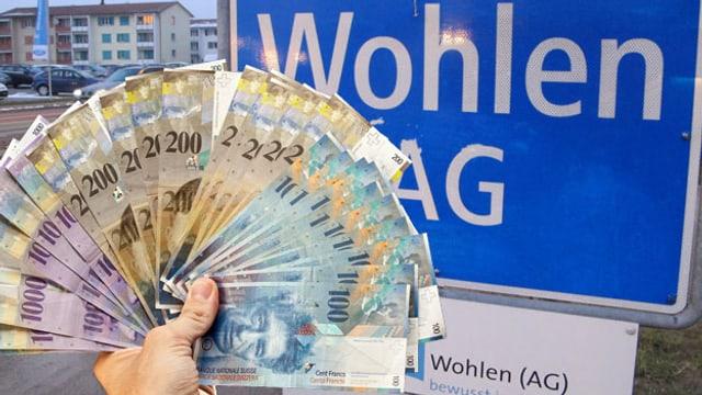 Eine Hand mit Banknoten vor dem Ortseingangsschild von Wohlen.