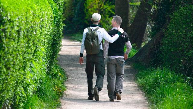 Zwei homosexuelle Männer, die als Paar erkennbar sind, auf einem Spazierweg.