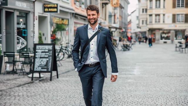 Mann in Anzug geht lachend durch Winterthurer Altstadt