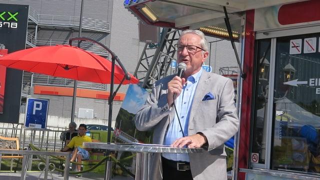 Ein Mann mit Brille, der in ein Mikrofon spricht.