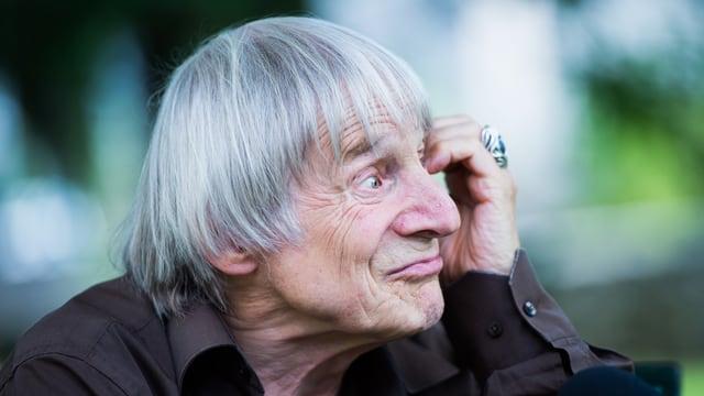 Ein Mann mit grauen Haaren stützt seinen Kopf mit der Hand.