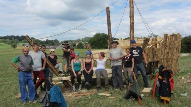 Helfer des Pfadilagers stehen vor einem selbstgebauten Holzschiff