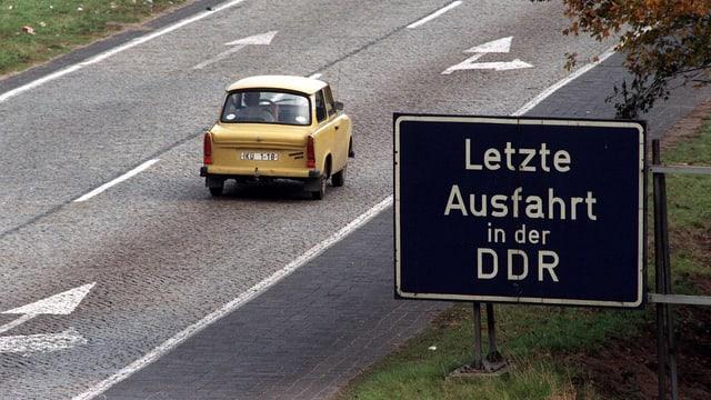 Strasse mit Trabi und Schild: «Letzte Ausfahrt in der DDR»