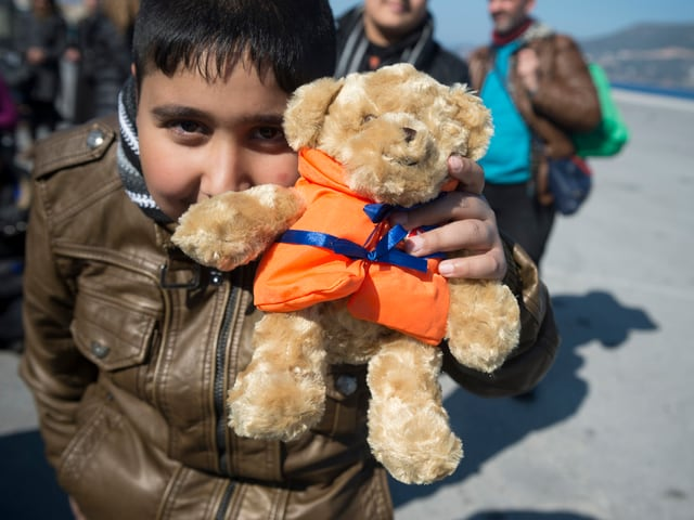 Ein Junge hält sich einen Teddybär mit orangefarbener Schwimmweste vor das Gesicht.