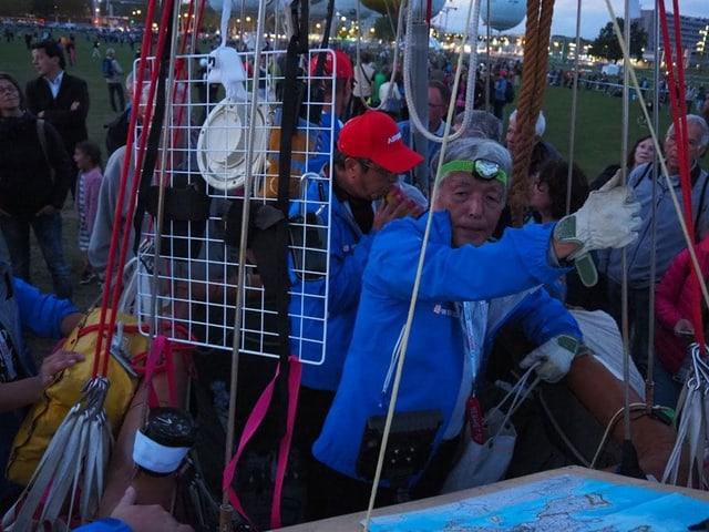 Pilot im blauen Overall im Korb vor dem Start.