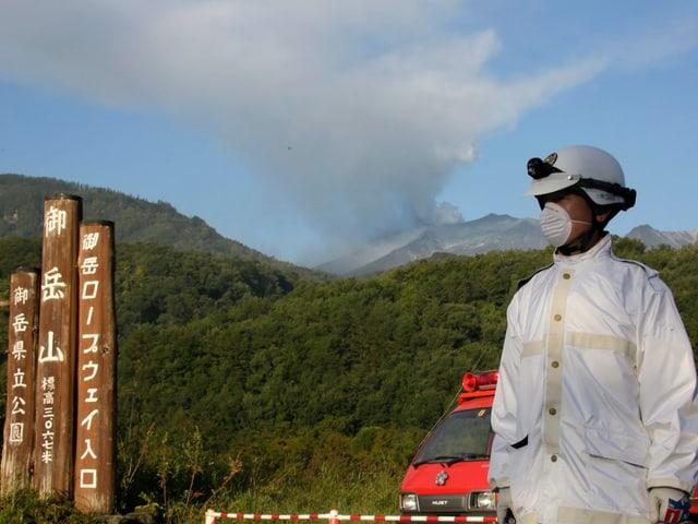 Ein Polizist mit Schutzanzug und Atemschutz sperrt die Zugangsstrasse zum Vulkan, der im Hintergrund raucht
