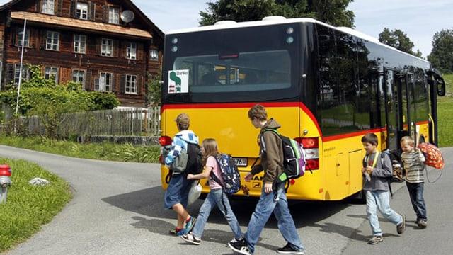 Schulkinder steigen aus einem Postauto aus.