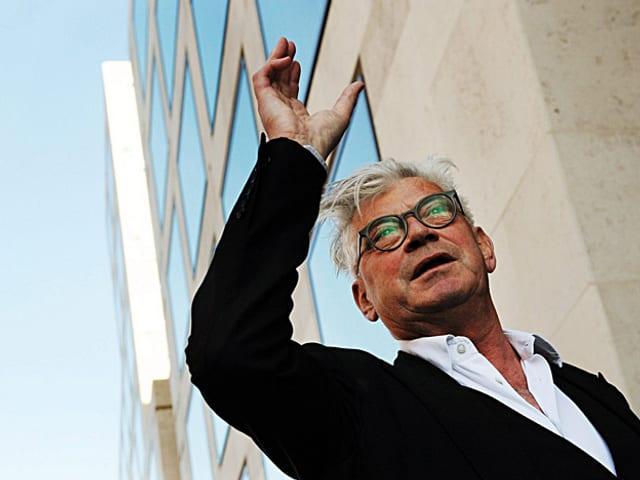 Der Architekt Max Dudler, mit erhobener rechter Hand seinen Bau erklärend.