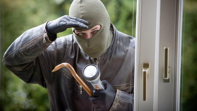 Ein Einbrecher mit Brecheisen schaut durch ein Fenster