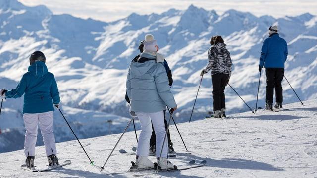 Skifahrer blicken auf die verschneite Bergwelt des Oberengadins.