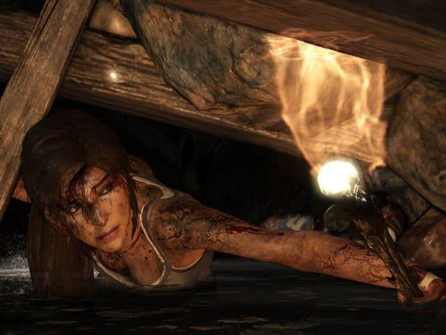 Ein Screenshot des Games «Tomb Raider» zeigt Lara Croft mit einer Fackel in der Hand.