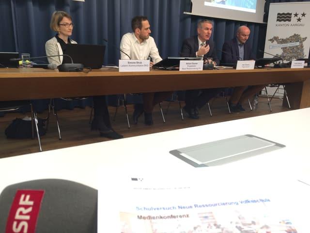 Medienkonferenz: Vier Leute sitzen an einem Tisch