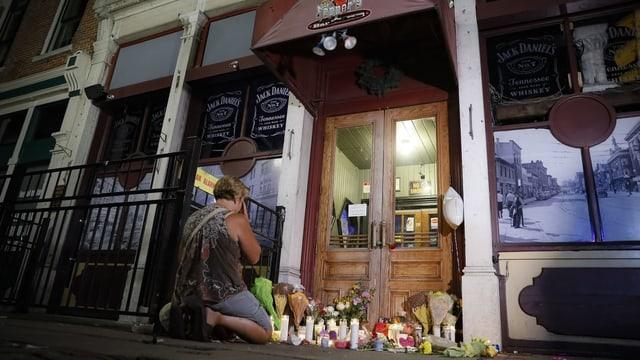 Frau kniet vor dem Eingang einer Bar. Am Boden viele Blumen und Gedenktafeln für die Toten.