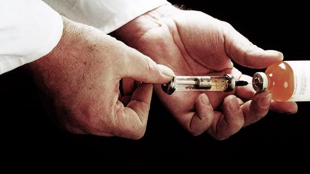 Mann mit weissem Kittel zieht eine Spritze auf.