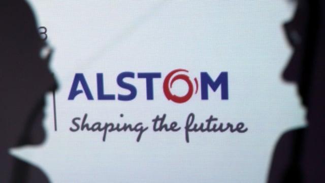 Die Silhouette von zwei Männern vor einem Alstom-Schriftzug