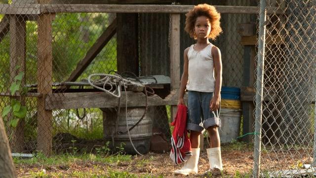 Ein kleines Mädchen steht in Gummistiefeln vor einem Stall.