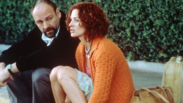 Ein Mann und eine Frau sitzen nebeneinander am Strassenrand.