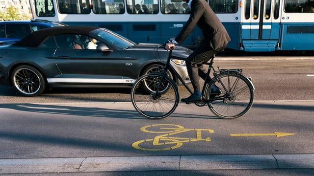 Ein Velofahrer fährt in entgegengesetzter Richtung wie Tram und Auto