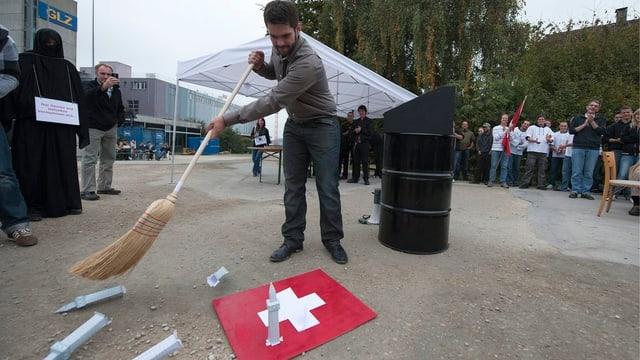 Dominic Lüthard wischt Minarette von einer Schweizer Fahne.