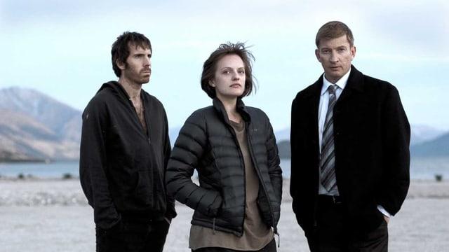 Zwei Männer und eine Frau stehen vor einem See.