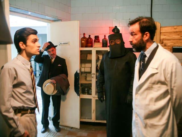 Ein Mann in einem weissen Kittel und ein jüngerer Herr stehen einander gegenüber.