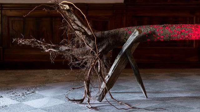 Ein bunt eingefärbter Baumstamm steht auf Holzbeinen.