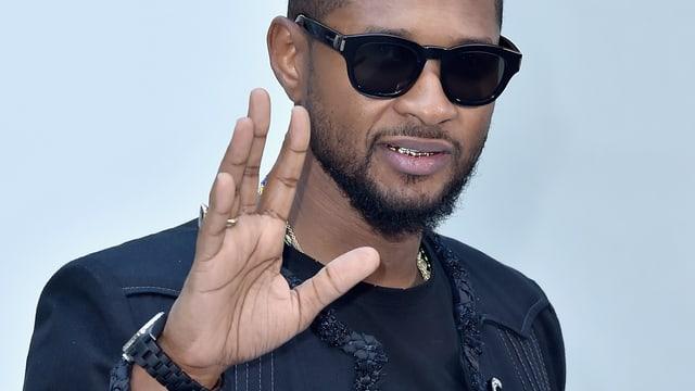 Ein Porträt von Usher. Er winkt und trägt eine schwarze Sonnenbrille.