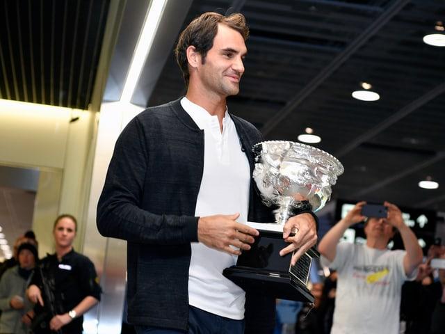 Roger Federer posiert mit dem Pokal.