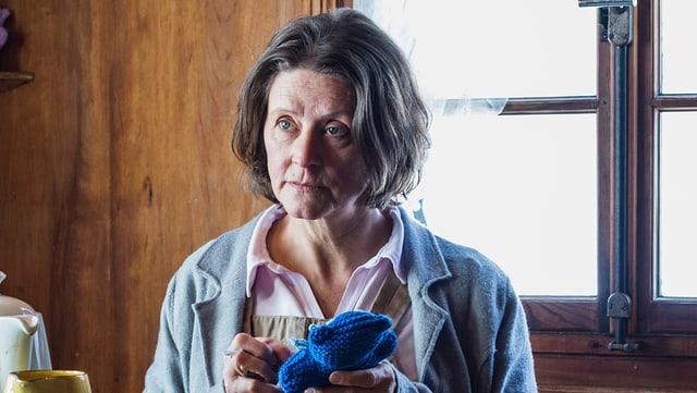 Eine Frau mit Strickzeug in einem Wohnzimmer