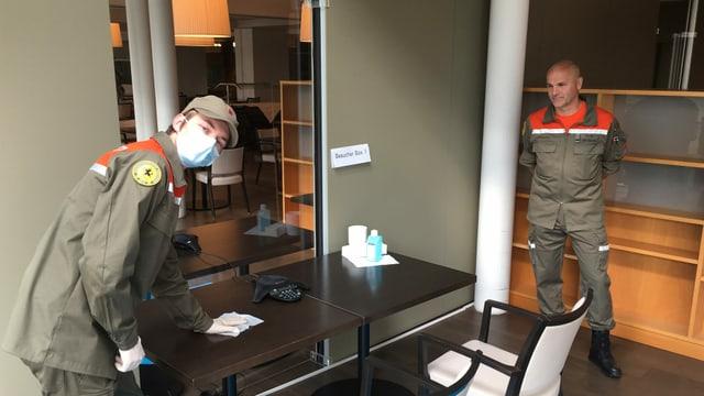Ein junger Mann mit Mundschutz in der orangen Zivilschutzuniform putzt einen Tisch in einem kleinen Raum.