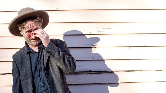 Ein Mann mit Hut und Sonnenbrille vor einer weissen Hauswand.