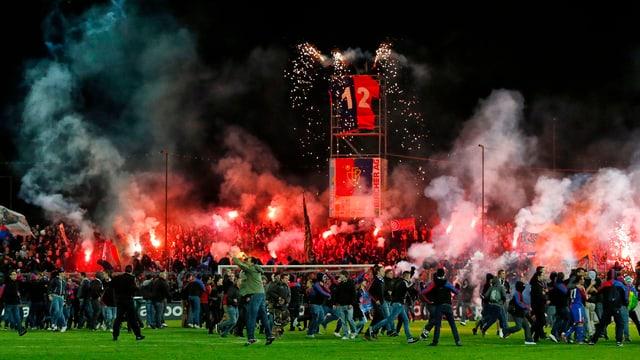 Fans stürmen Spielfeld, im Hintergrund Rauch und rotes Feuer.