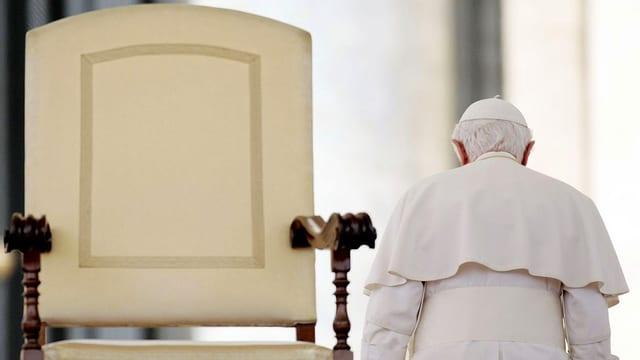 Papst Benedikt XVI. von hinten neben einem grossen Stuhl