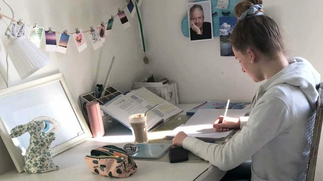 Eine junge Frau sitz an einem Schreibtisch.