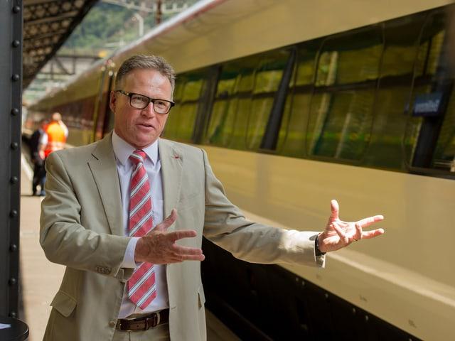SBB-Chef Andreas Meyer steht gestikulierend neben einem Neigezug