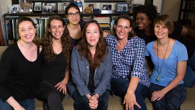 Eine Gruppe von Frauen, lachend auf einem Sofa.